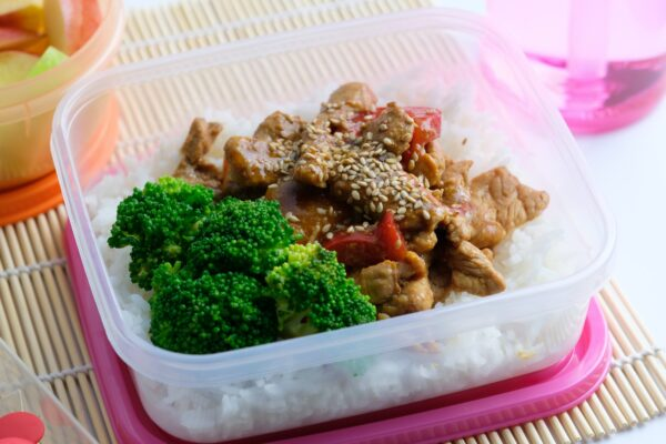 Asian style lunch box with sesame pork and broccoli