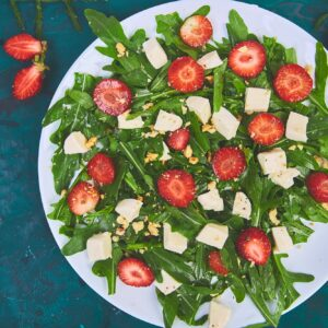 Fresh salad with arugula, strawberries, feta cheese and nuts.