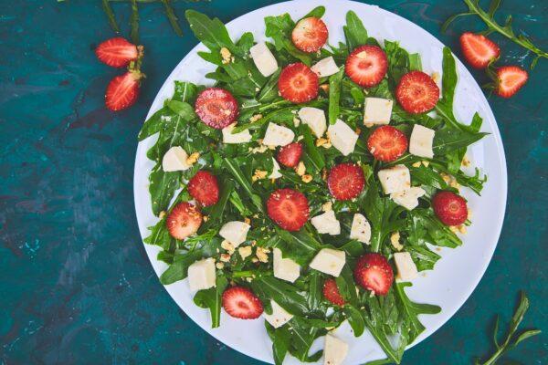 Fresh salad with arugula, strawberries, feta cheese and nuts.